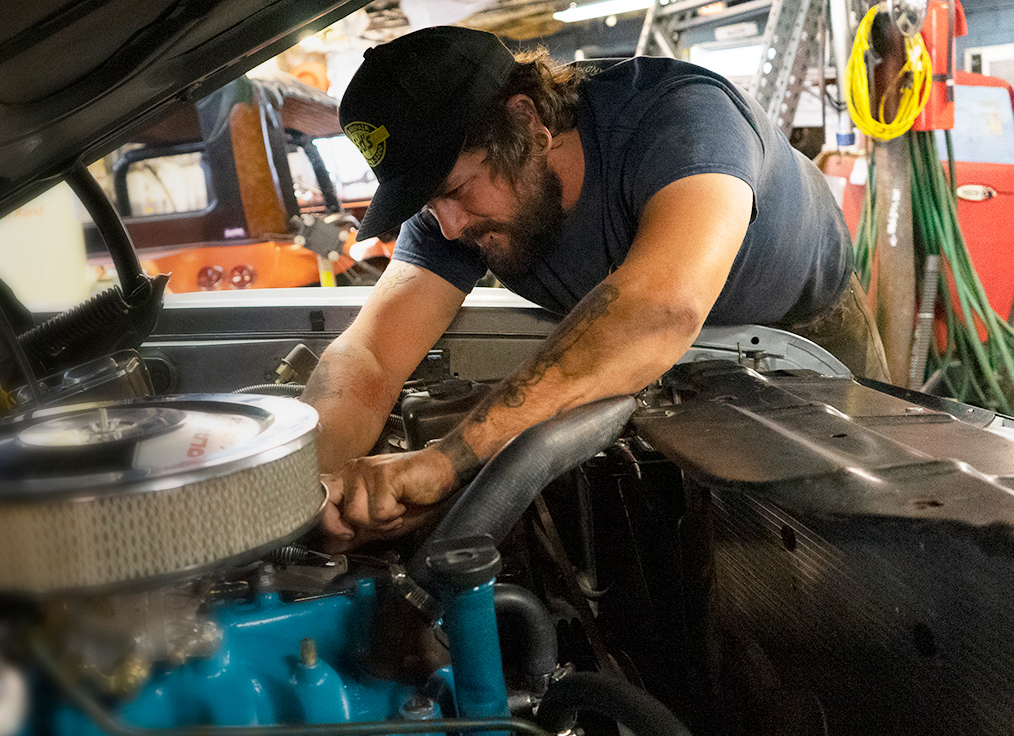 An auto mechanic at Sid's Auto working under the hood of a car.