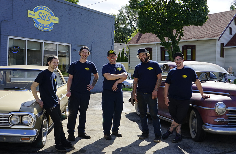 Smiling employees standing outside of Sid's Auto Repair.